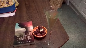 Picture of a glass of fizz, chocolates and the book The Last Gatekeeper